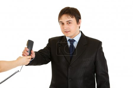 Smiling young businessman taking phone from secretary