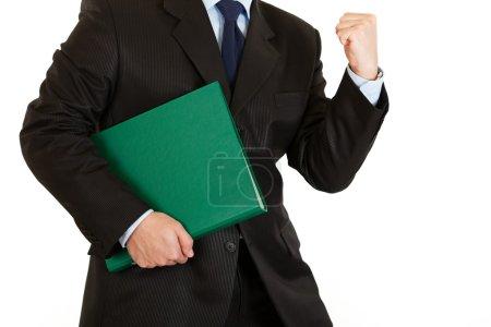 Pleased modern businessman holding folder. Close-up.