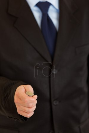Heads or tails? Businessman holding euro coin on hand. Close-up.