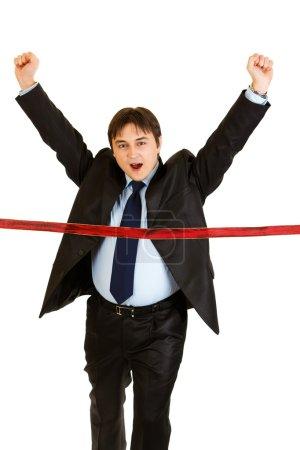 Pleased young businessman crossing finish line. Concept - success achievem