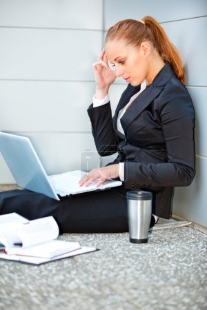 Concentrated business woman sitting on floor at office building and using