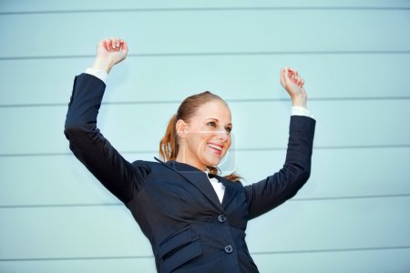 Femme d'affaires excitée debout à l'immeuble de bureaux et se réjouissant de sa succion
