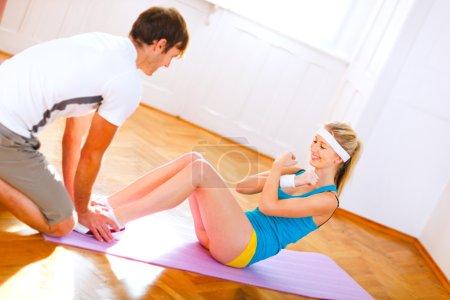 Man helping slim girl making abdominal crunch