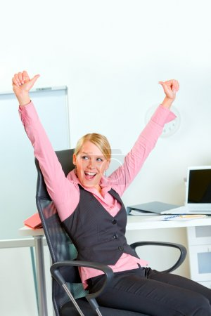 Happy business woman sitting at workplace rejoicing success