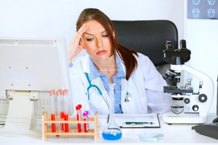 Concerned doctor woman sitting at office table and holding hand