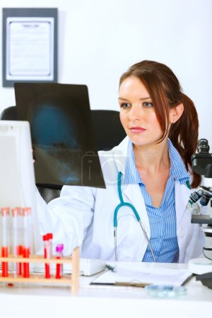 Doctor woman sitting at office table and analyzing patients roen