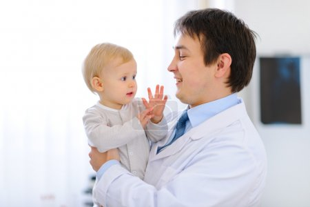 Portrait of pediatrician with baby on hands