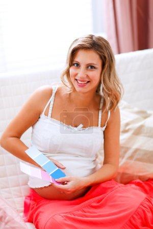 Photo pour Heureuse femme enceinte assise sur le canapé avec des échantillons de peinture - image libre de droit