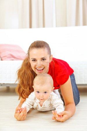 Photo pour Maman souriante et adorable bébé jouant sur le sol - image libre de droit