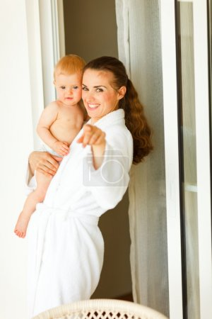 Portrait of young mama in bathrobe with baby in hand pointing in camera