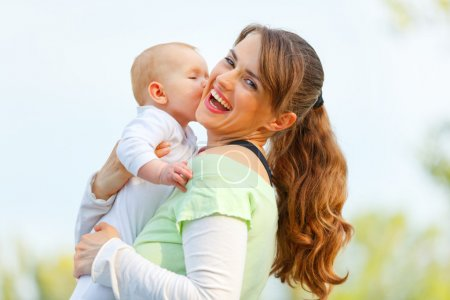 Laughing mother hugging her baby in hands outdoors