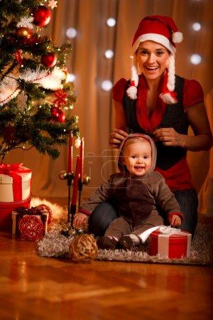 Photo pour Heureuse mère et bébé adorable dans le costume de petit assistant du père Noël - image libre de droit