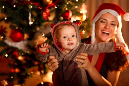 Photo for Happy mother playing with baby near Christmas tree - Royalty Free Image