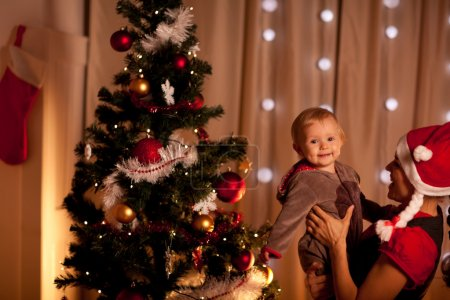 Photo for Portrait of lovely baby on mamas hand near Christmas tree - Royalty Free Image