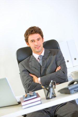 Portrait of modern businessman sitting at office desk