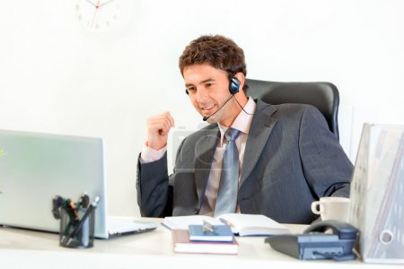 Smiling businessman with headset sitting at office desk and looking on lap