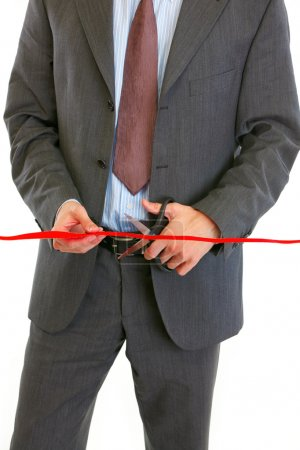 Closeup on businessman cutting red ribbon