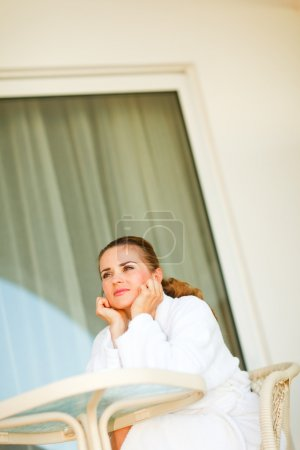 Smiling attractive female in bathrobe sitting at table on terrac