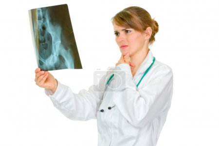Concentrated medical female doctor analyzing patients roentgen