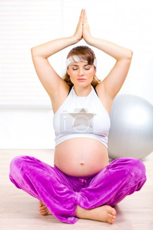 Beautiful pregnant woman doing yoga exercises on floor at home