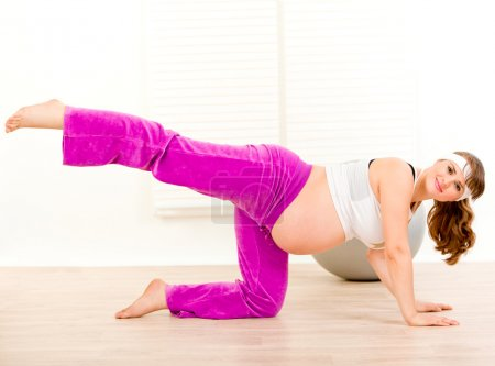 Smiling charming pregnant woman doing fitness exercises at home