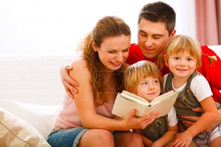 Photo pour Heureux parents qui lisent avec filles de jumeaux - image libre de droit