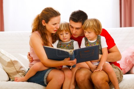 Mother and father looking photo album with twins daughters