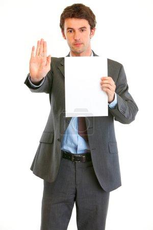 Photo pour Homme d'affaires moderne sérieux tenant du papier blanc et montrant un geste d'arrêt - image libre de droit