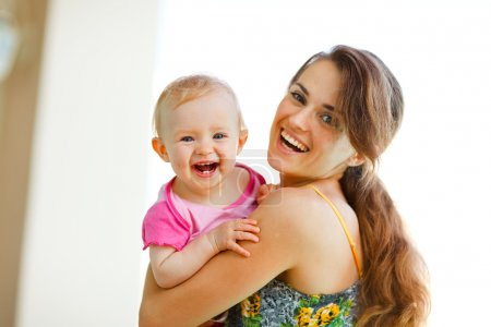 Portrait of laughing mother and baby