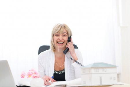 Happy senior architect woman having good news phone call