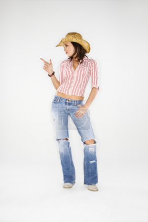 Photo pour Jeune femme blanche adulte portant un chapeau de cow-boy pointant du doigt comme un pistolet . - image libre de droit