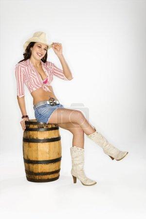 Photo pour Jeune femme caucasienne habillée en cow-girl assise sur un tonneau et un chapeau inclinable au spectateur . - image libre de droit