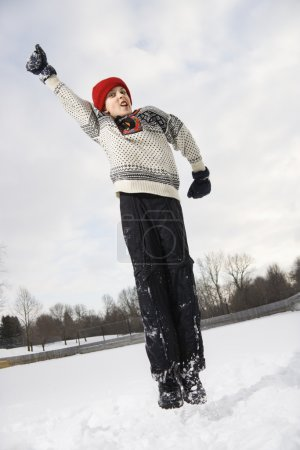 Photo pour Garçon caucasien portant un pull et une casquette rouge d'hiver sautant dans l'air avec le bras tendu . - image libre de droit
