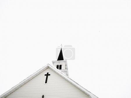 Photo pour Haut de l'église blanche avec quelques éclaircies en arrière-plan. - image libre de droit