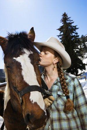 Foto de Atractiva joven con sombrero de vaquero y besar a un caballo. Disparo vertical . - Imagen libre de derechos