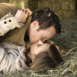 Young adult Caucasian couple lying down in hay kis...
