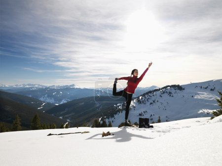 Photo for Young woman doing yoga pose on rock in snow in mountainous terrain. - Royalty Free Image