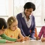 Teacher helping students in school classroom. Hori...