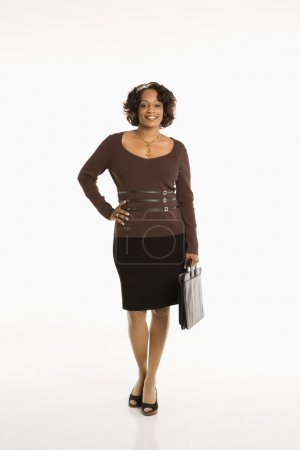 Photo for Full length portrait of businesswoman standing with hand on hip holding briefcase. - Royalty Free Image