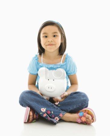 Girl holding piggybank.