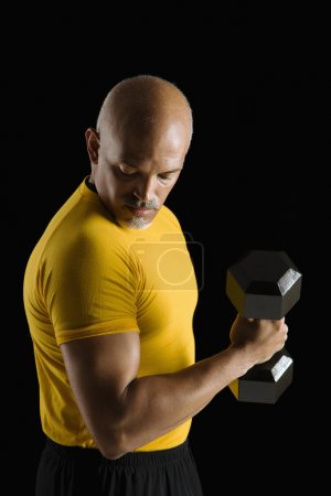 Man exercising with dumbbell.