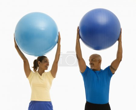 Photo for Happy smiling mid adult multiethnic man and woman holding blue exercise balls over their heads looking at each other. - Royalty Free Image