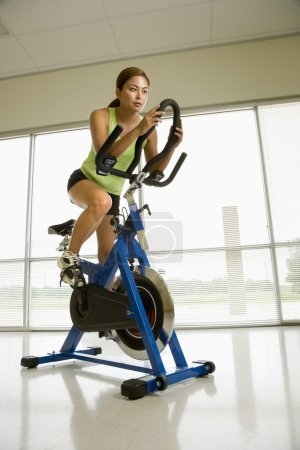 Photo for Mid adult Asian woman pedaling exercise bicycle indoors. - Royalty Free Image