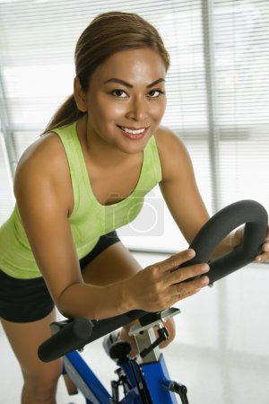 Photo for Mid adult Asian woman pedaling exercise bicycle smiling at viewer. - Royalty Free Image