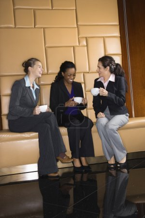 Photo for Businesswomen drinking coffee and conversing. - Royalty Free Image