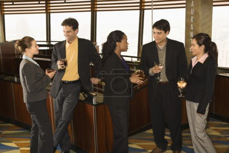 Photo for Ethnically diverse group of businesspeople in bar drinking and conversing. - Royalty Free Image