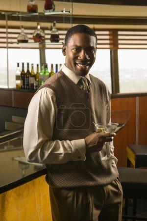 Foto de Afro americano medio hombre adulto en el bar con martini sonriendo al espectador - Imagen libre de derechos