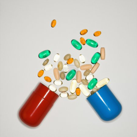 Photo for Container with spilt pills and vitamins. - Royalty Free Image