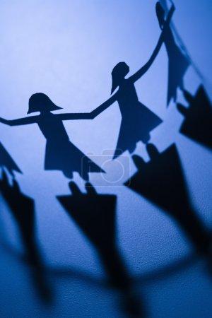 Photo pour Papier découpé femelles debout tenant la main . - image libre de droit