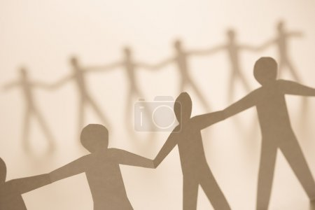 Photo for Cutout paper men standing holding hands. - Royalty Free Image